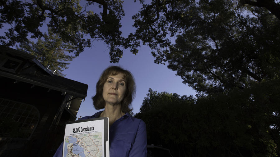 Rachel Kellerman with a graphic showing points where over 40,000 complaints to the FAA were logged in front of her home in Palo Alto. (Brian van der Brug / Los Angeles Times)
