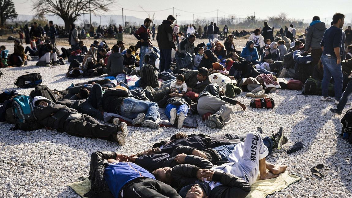 Migrants and refugees, many of them Syrian, rest on the ground as they wait to enter a registration camp after crossing the Greek-Macedonian border on Nov. 18. (Dimitar Dilkoff / AFP/Getty Images)