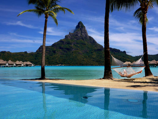 <p>A guest reads a book on the beach at the InterContinental Bora Bora Resort and Thalasso Spa, commonly called the Thalasso, in Bora-Bora. Mt. Otemanu looms in the background.</p>