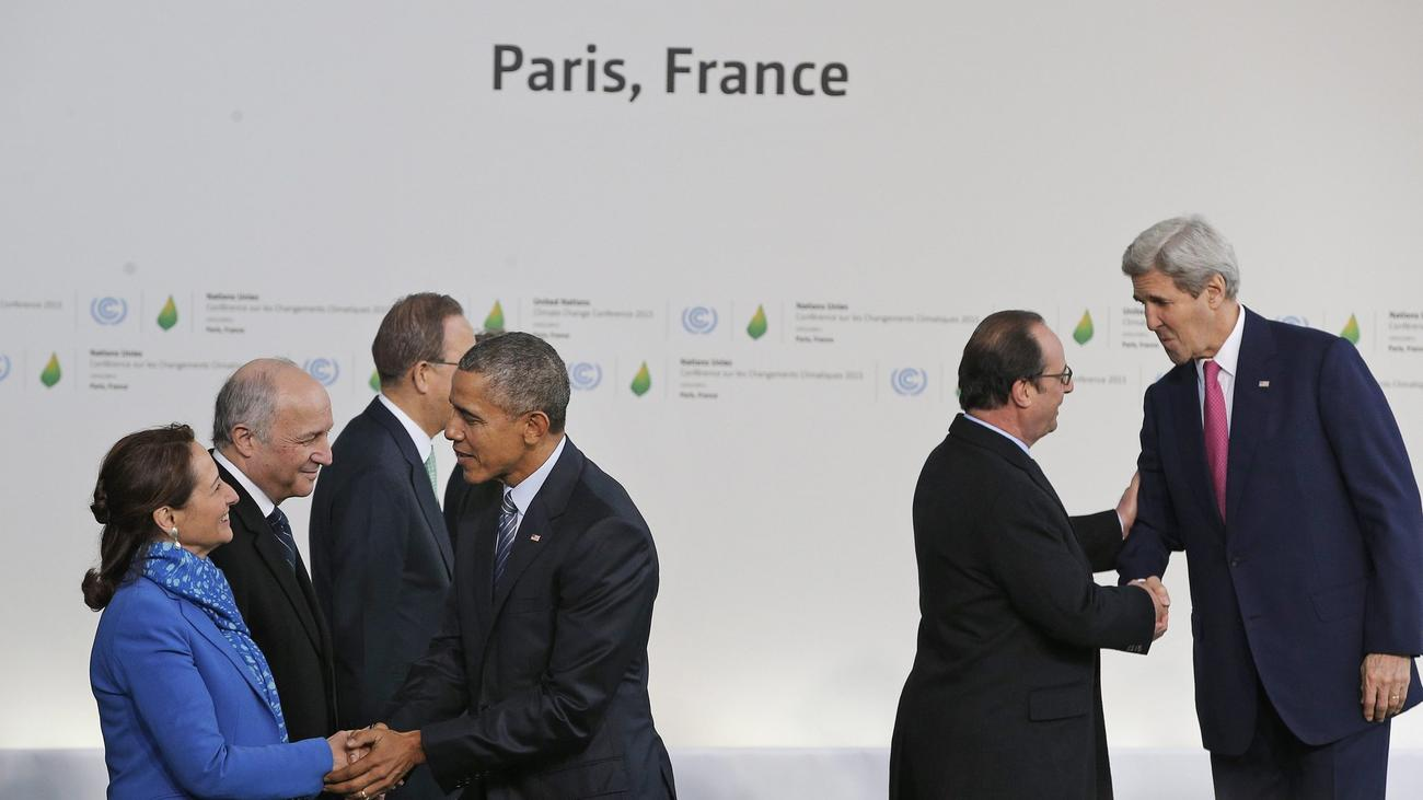 President Obama is greeted by Segolene Royal, left, French minister for ecology, sustainable development and energy, and Secretary of State John Kerry is greeted by French President Francois Hollande as they arrive in Paris on Nov. 30 for the climate change conference. (Christophe Ena / European Pressphoto Agency)