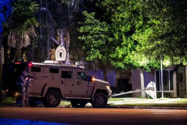 A SWAT team outside a residence in Redlands on Wednesday night. (Marcus Yam / Los Angeles Times)