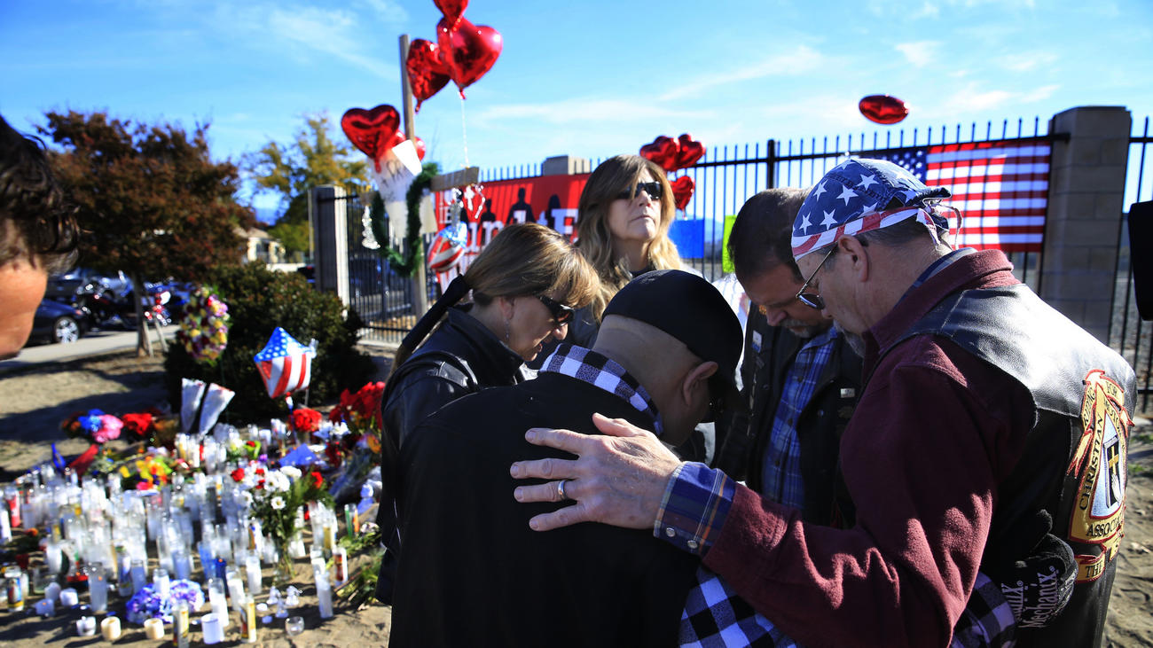 Riders from the Christian Motorcycle Assn. in San Bernardino pray at a makeshift memorial for the victims after the shooting at the Inland Regional Center. (Allen J. Schaben / Los Angeles Times)