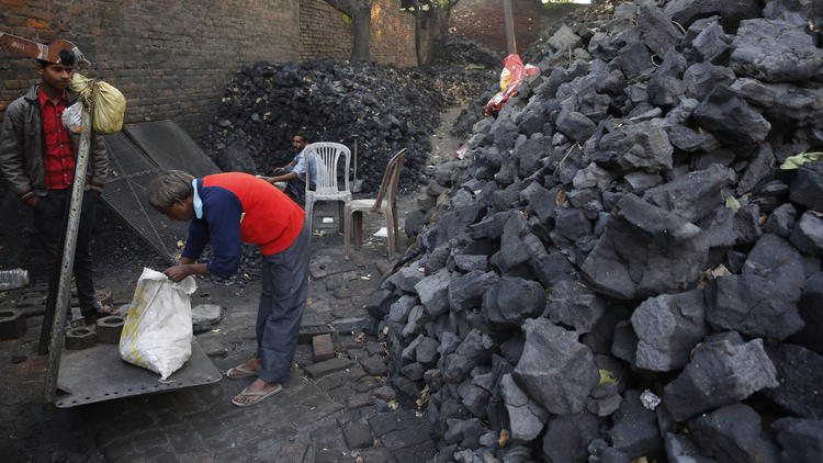 An Indian coal vendor weighs coal for a customer in Lucknow on Dec. 3. (Rajesh Kumar Singh / Associated Press)