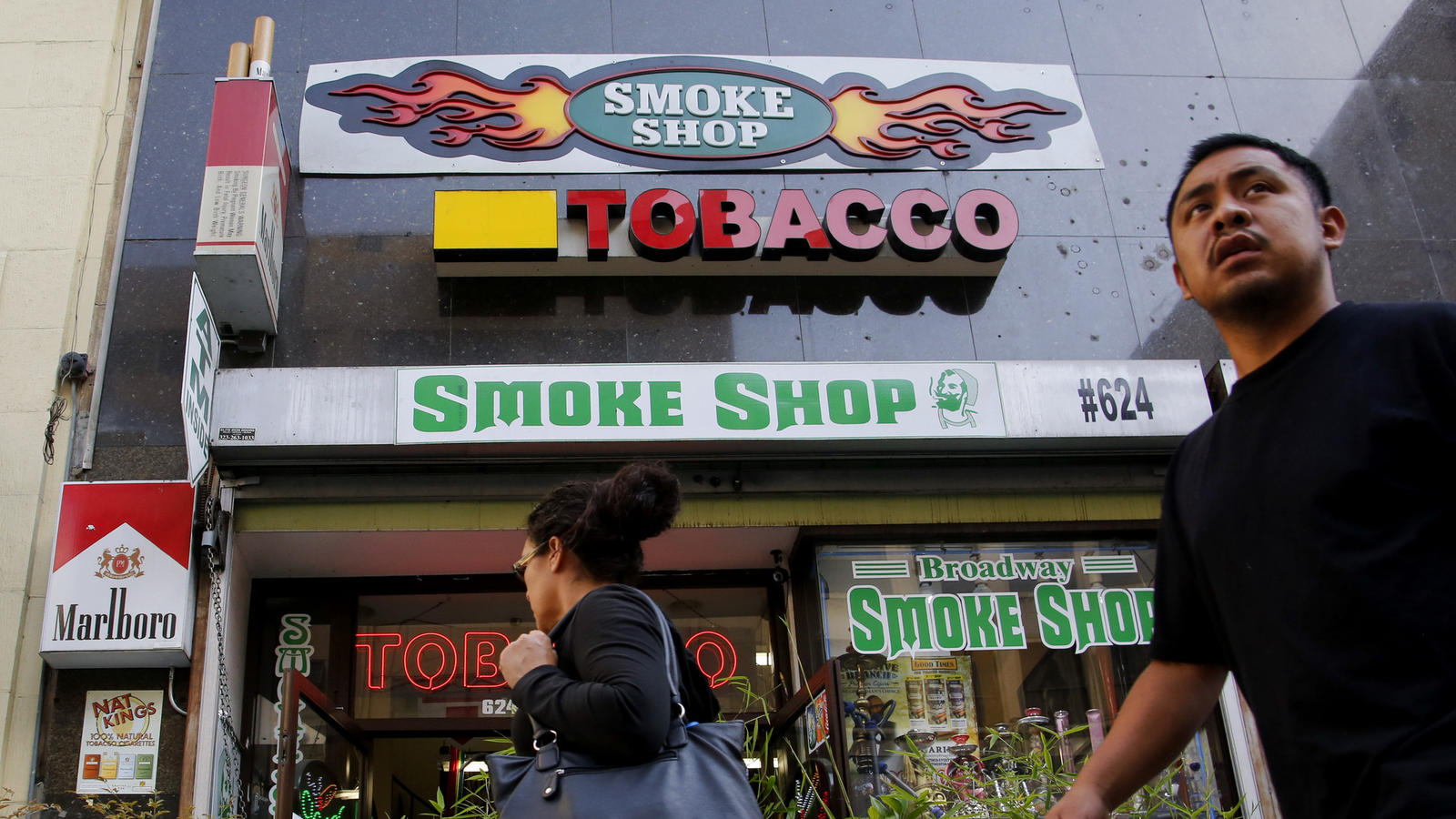 Pedestrians pass by a smoke shop on Broadway in downtown Los Angeles in 2014. (Los Angeles Times)