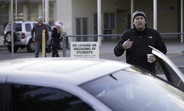 Hale Charter Academy Principal Chris Perdigao tells parents that the Woodland Hills campus is closed. (Brian van der Brug / Los Angeles Times)