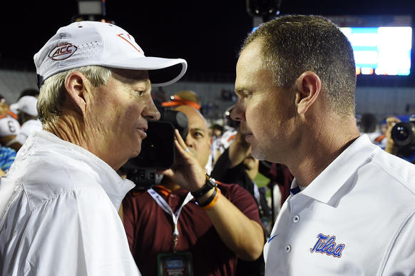 SHREVEPORT, LA - DECEMBER 26: Head coach Frank Beamer of the Virginia Tech Hokies (L) greets head coach Philip Montgomery of the Tulsa Golden Hurricane at midfield following the Camping World Independence Bowl on December 26, 2015 in Shreveport, Louisiana.  Virginia Tech won the game 55-52.  (Photo by Stacy Revere/Getty Images) ORG XMIT: 596636429