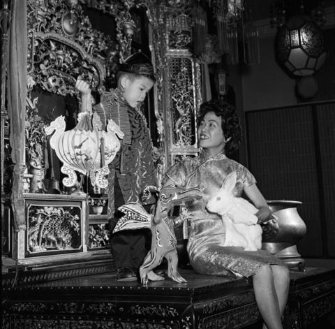 """Miss Chinese New Year Ming-Cho Lee, right, talks to Ed Tom, 5, on February 11, 1964. Lee holds a rabbit and a toy dragon in hand, greeting the new """"Year of the Dragon"""" and saying goodbye to the """"Year of the Rabbit."""""""