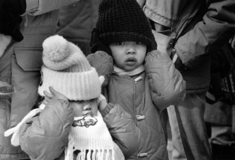 Toddlers try to block out the noise of firecrackers as Chicago's Chinese community ushers in the Year of the Tiger on Feb. 9, 1986, during the Chinese New Year parade on Argyle Street in Chicago.
