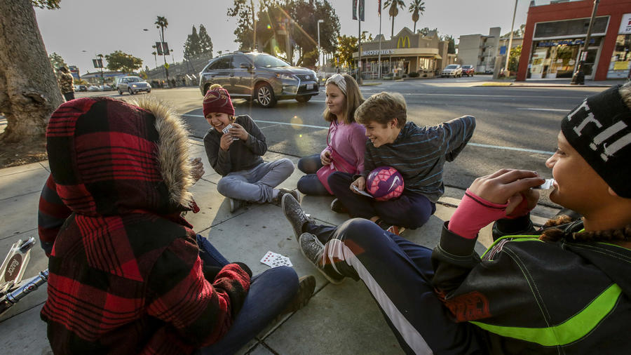 Christianna Watkins, 12, right, from Lake Elsinore, and her friends play a card game sitting along Colorado Boulevard in advance of Friday's parade. (Irfan Khan / Los Angeles Times)