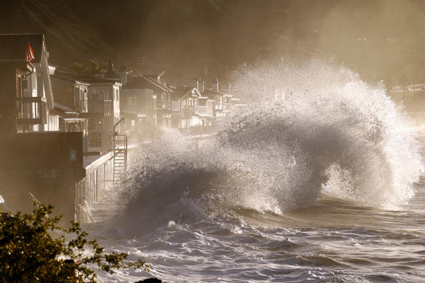 Forceful and beautiful waves crash into the sea walls of homes at Mondos Beach under the mountains of the recent Solimar fire at high tide sunrise west of Ventura on Thursday morning. (Al Seib / Los Angeles Times)