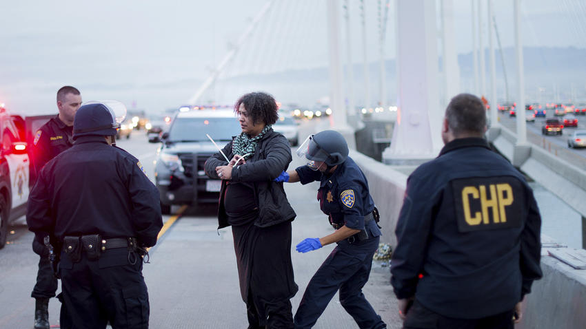 A California Highway Patrol officer detains a protester on the San Francisco-Oakland Bay Bridge.