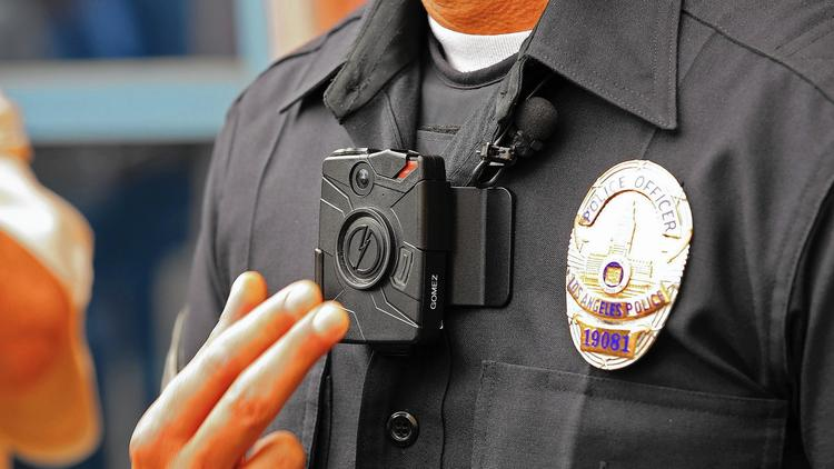 LAPD Officer Jim Stover demonstrates how an officer turns on the new Taser body camera at a news conference in 2015. (Al Seib / Los Angeles Times)