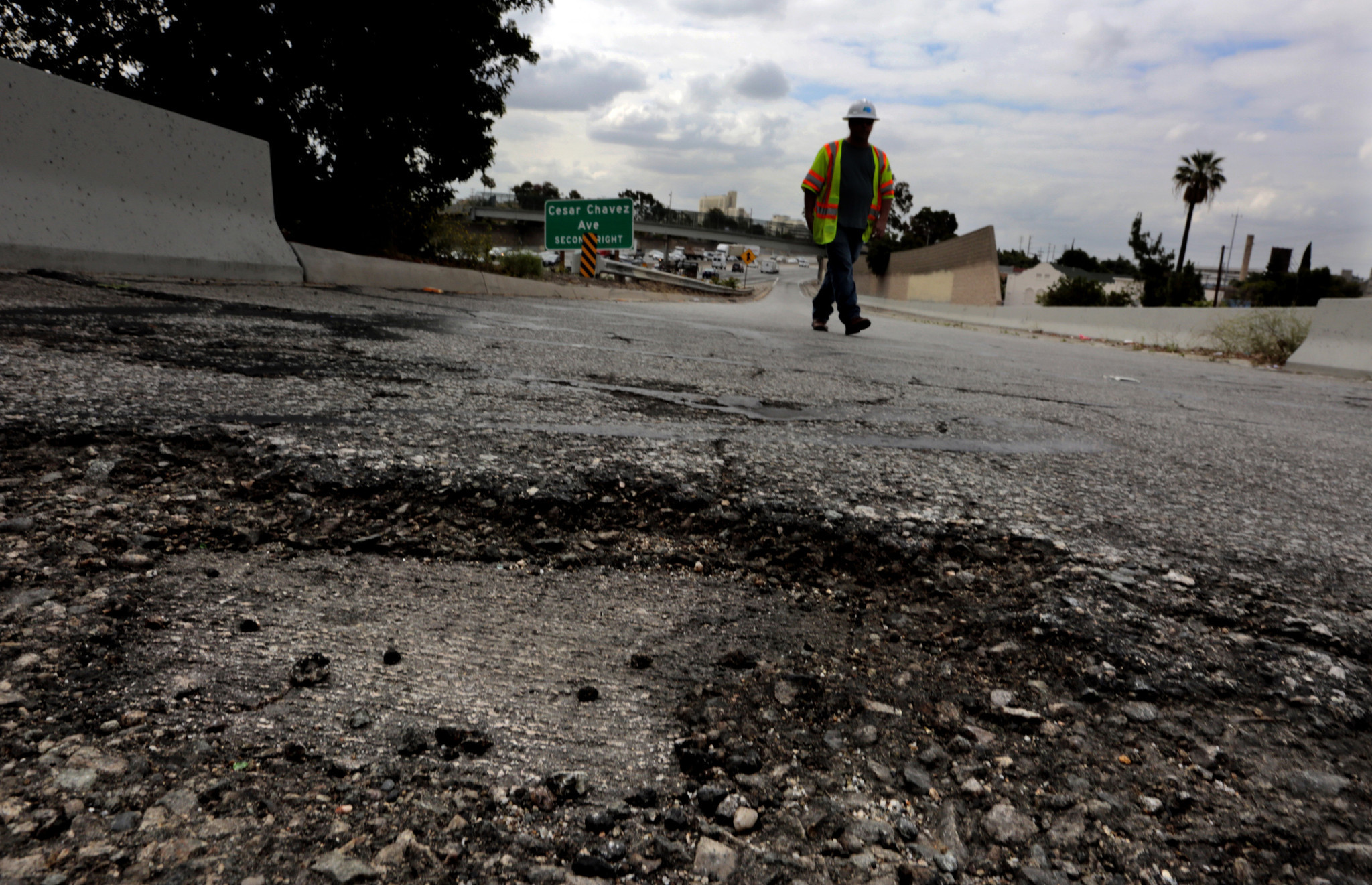 A Caltrans maintenance supervisor walks along a portion of a southbound 5 Freeway onramp where potholes and cracks are common in 2015. (Los Angeles Times)