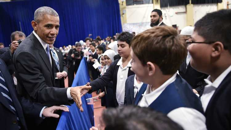 President Obama greets students earlier this week at a Baltimore mosque, where he offered the kind of upbeat message he hopes fellow Democrats will embrace — especially on the campaign trail. (Mandel Ngan / AFP-Getty Images)