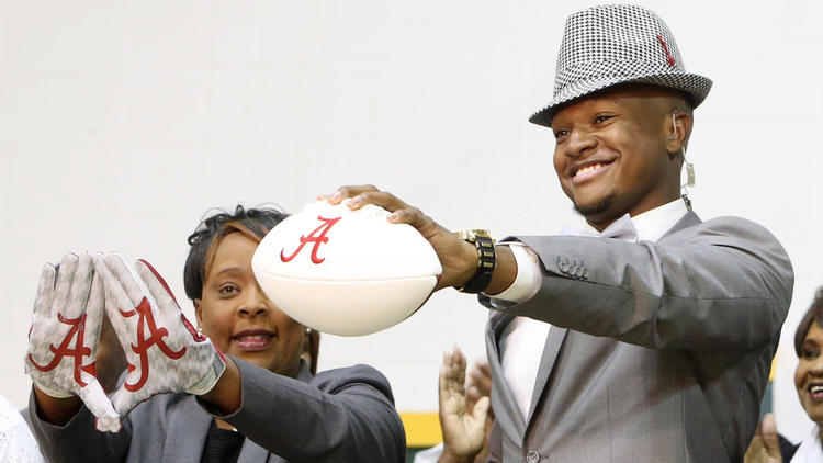 Gordo High (Ala.) football player Ben Davis holds up a football with the Alabama symbol on national signing day while dressed like legendary Crimson Tide coach Bear Bryant. (Michelle Lepianka Carter / Associated Press)