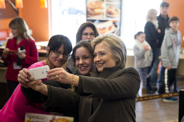 Hillary Clinton takes a selfie with customers at a Dunkin Donuts in Manchester, N.H., Sunday. (Matt Rourke / AP)