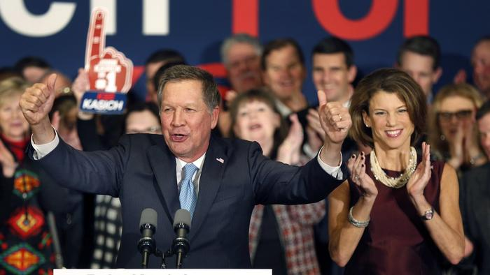 With his wife, Karen, at his side Republican presidential candidate Gov. John Kasich of Ohio cheers with supporters Tuesday in Concord, N.H., at his primary night rally. (Jim Cole / Associated Press)