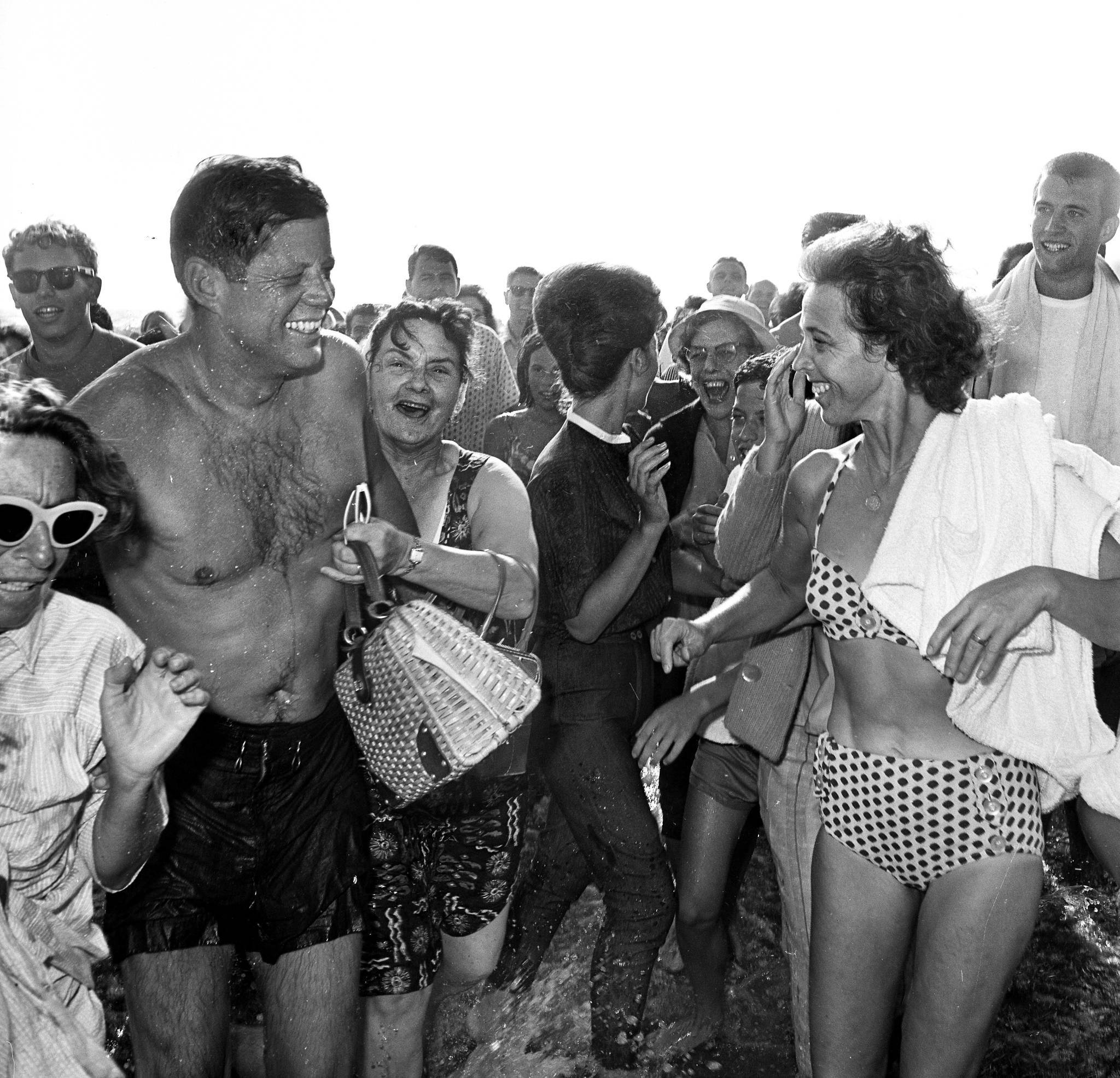To cap off a 33-hour visit to Los Angeles in 1962, President Kennedy takes an impromptu dip at the beach in Santa Monica as throngs of admirers try to get close.