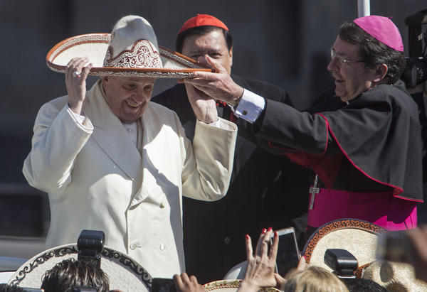 Pope Francis dons a Mexican charro-style sombrero given to him by a person in the crowd in Mexico City's main square, the Zocalo. (Christian Palma / Associated Press)
