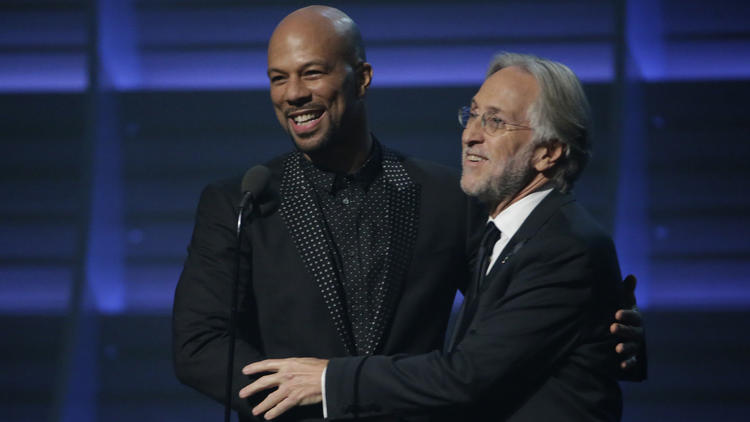 Common, left, and Recording Academy President Neil Portnow embrace at the 58th Grammy Awards at Staples Center on Monday. (Robert Gauthier / Los Angeles Times)