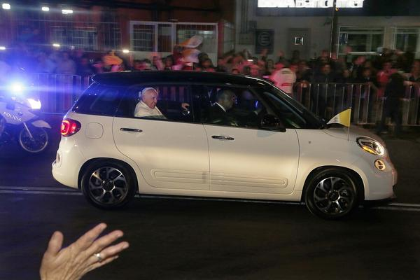 Pope Francis waves from a Fiat on his way to the Vatican's diplomatic mission in Mexico City. (Marco Ugarte / Associated Press)