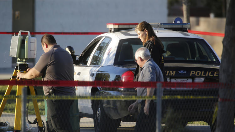 Investigators pass the patrol car at the site where an Anaheim police officer shot and killed a 22-year-old man in Sage Park in Anaheim on Feb. 9 (Mark Boster / Los Angeles Times)