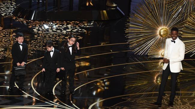Oscars host Chris Rock introduces children representing PricewaterhouseCoopers accountants at the 88th Oscars on Sunday. (Mark Ralston / AFP / Getty Images)