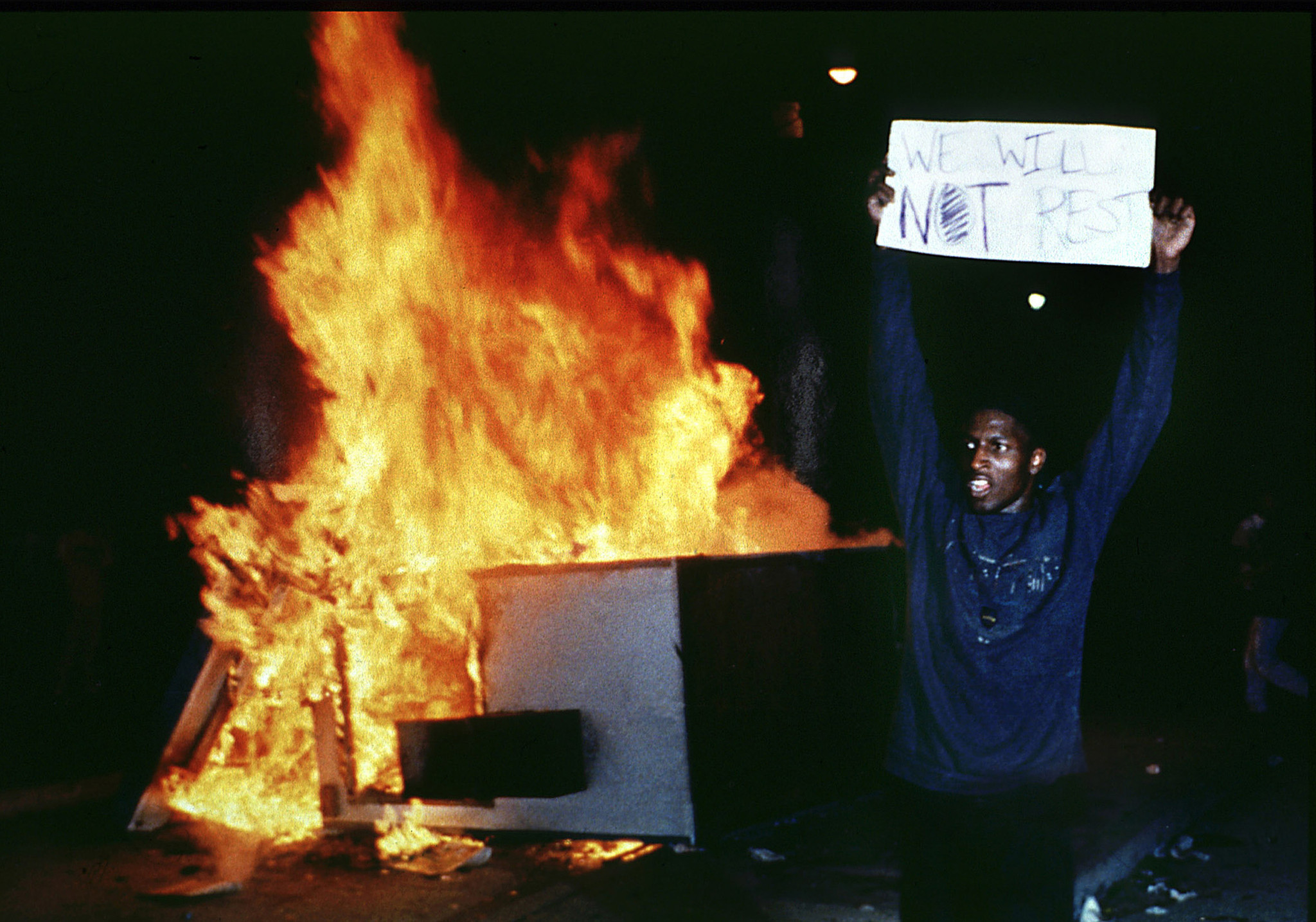 "A photograph taken near City Hall the night of the verdict, with a young man holding a sign that says ""We will not rest."""