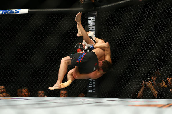 Darren Elkins (top) slams Chas Skelly to the canvas. (Rey Del Rio / Getty Images)