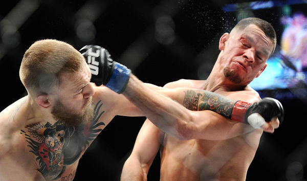 Conor McGregor, left, and Nate Diaz exchange punches. (Wally Skalij / Los Angeles times)