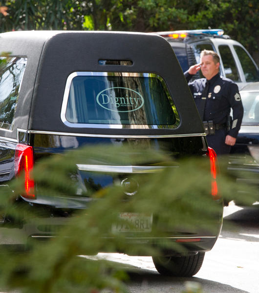 A police officer salutes as a hearse leaves the Malibu home of Nancy Reagan. (Michael Owen Baker / For The Times)