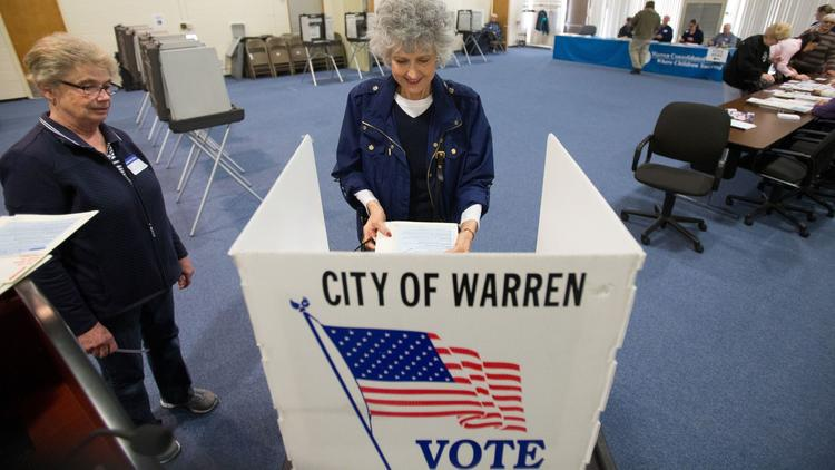 People vote in Warren, Mich., in the state's presidential primary. (Geoff Robins / AFP-Getty Images)