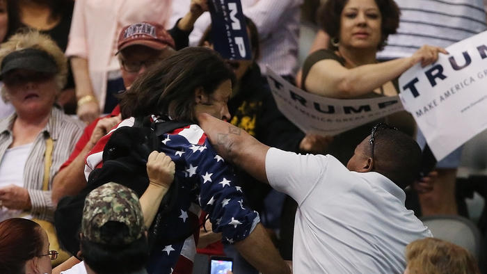 Protester Bryan Sanders, center left, is punched by a supporter of Donald Trump as he is escorted out of Republican presidential candidate's rally at the Tucson Arena on March 19. (Mike Christy / Associated Press)