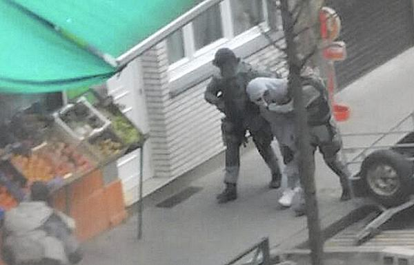 Police detain a man in Brussels' Molenbeek district on March 19 who is believed to be connected to a suspect in the Paris attacks. Residents say the district shouldn't be demonized for the actions of a few. (Zouheir Ambar / Associated Press)