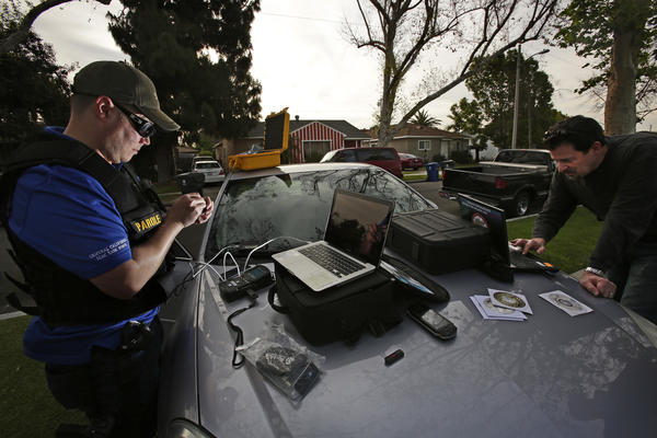 Parole agents use a Cellebrite and a laptop to check a sex offender's mobile phone, thumb drives and laptop for pornographic material during a sweep in April 2014.