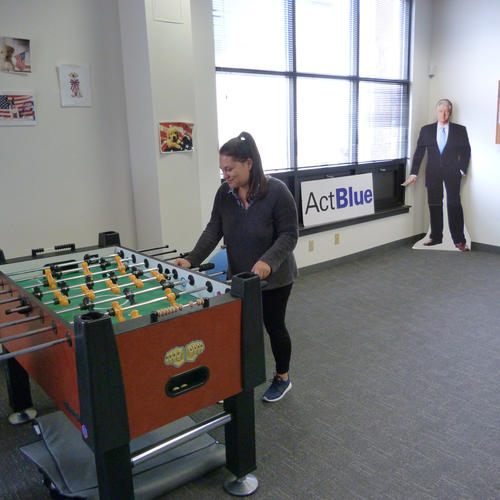 Marketing manager Hannah Brown hits the foosball table at ActBlue's Somerville, Mass., headquarters. Behind her is a cardboard cutout of Bill Clinton. (Evan Halper / Los Angeles Times)