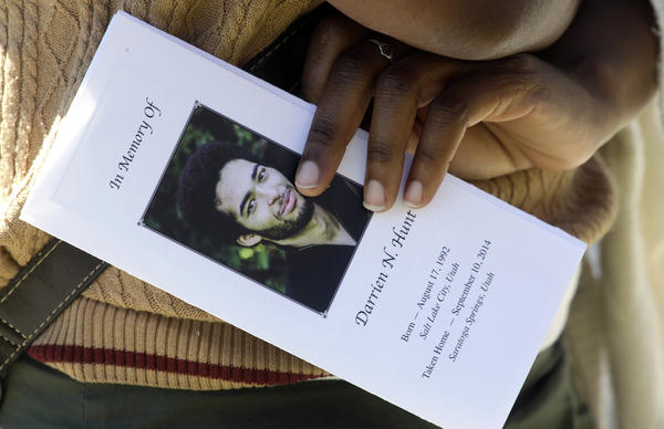 A mourner holds the funeral program for Darrien Hunt, who was shot and killed by police while holding a costume samurai sword, at services in Saratoga Springs, Utah