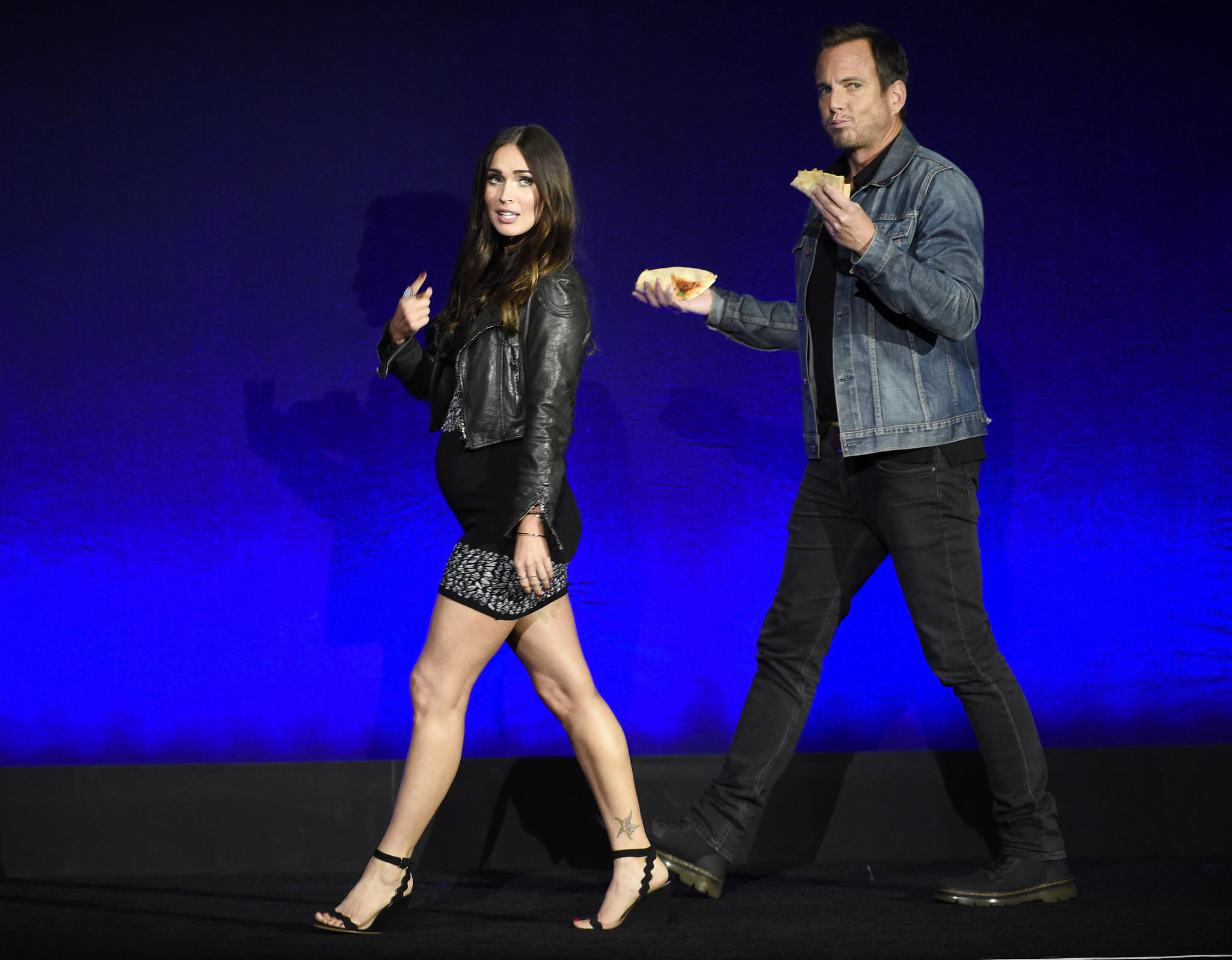 "Megan Fox and Will Arnett, cast members in the upcoming film ""Teenage Mutant Ninja Turtles: Out of the Shadows,"" take the stage during the Paramount Pictures presentation at CinemaCon 2016. (Chris Pizzello / Invision / AP)"