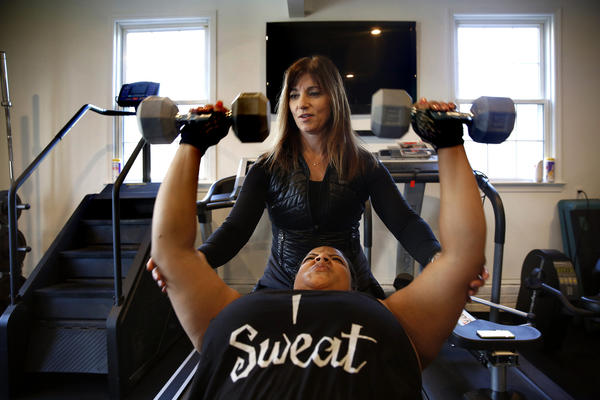 Personal trainer Peggy Hayes works with a client at her home gym. Hayes supports Donald Trump for president.