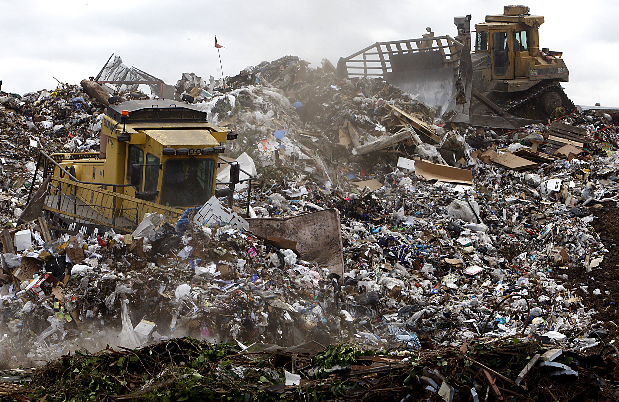 Heavy equipment operators use machinery to compact and shape mountains of trash at L.A. County's Puente Hills Landfill.