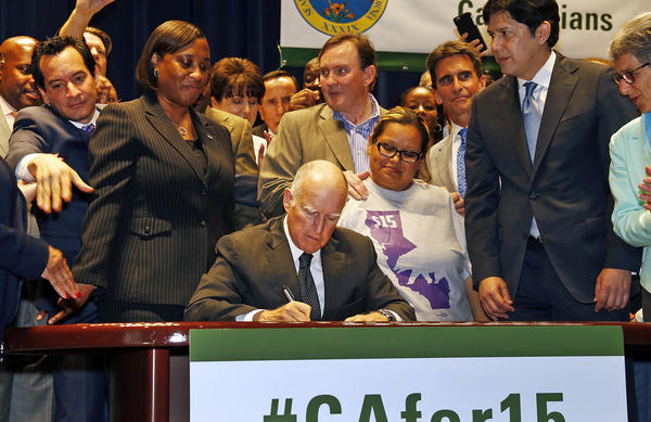 California Gov. Jerry Brown signs the minimum wage bill, raising the wage to $15 an hour by 2022.