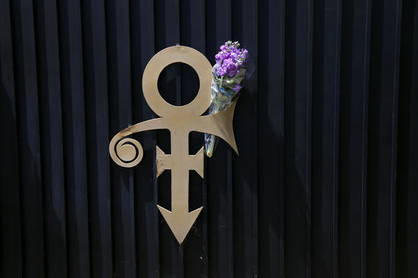 A fresh bouquet of flowers adorns the symbol Prince once changed his name to that is attached to the exterior of a home at the intersection of Bennett and Broadway in Long Beach. (Rick Loomis / Los Angeles Times)