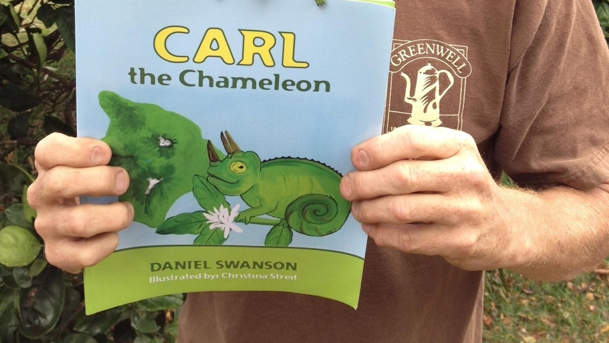 "Author Daniel Swanson holds a copy of his first children's book, a work of fiction about the very real ""Carl the Chameleon."""