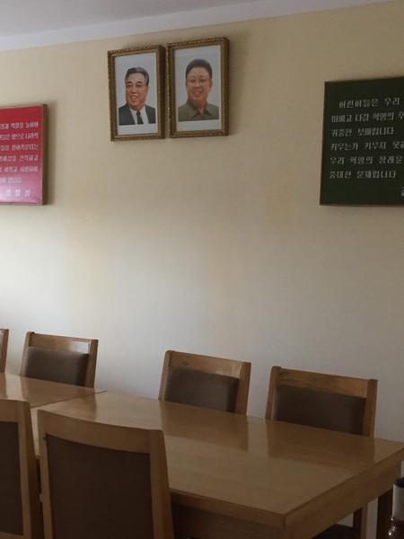Portraits of Kim Il Sung and Kim Jong Il hang on the wall at the Changchon nursery school.