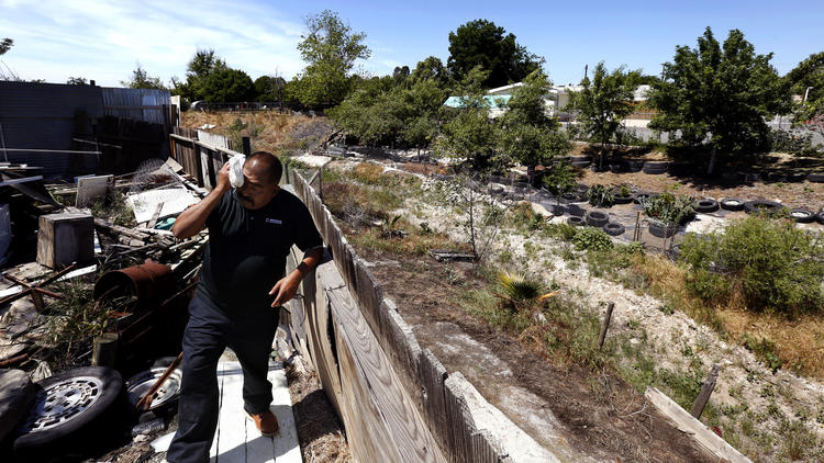 Tomas Garcia has been without running water for the last two years. He gets by with a water tank in his frontyard. (Genaro Molina / Los Angeles Times)