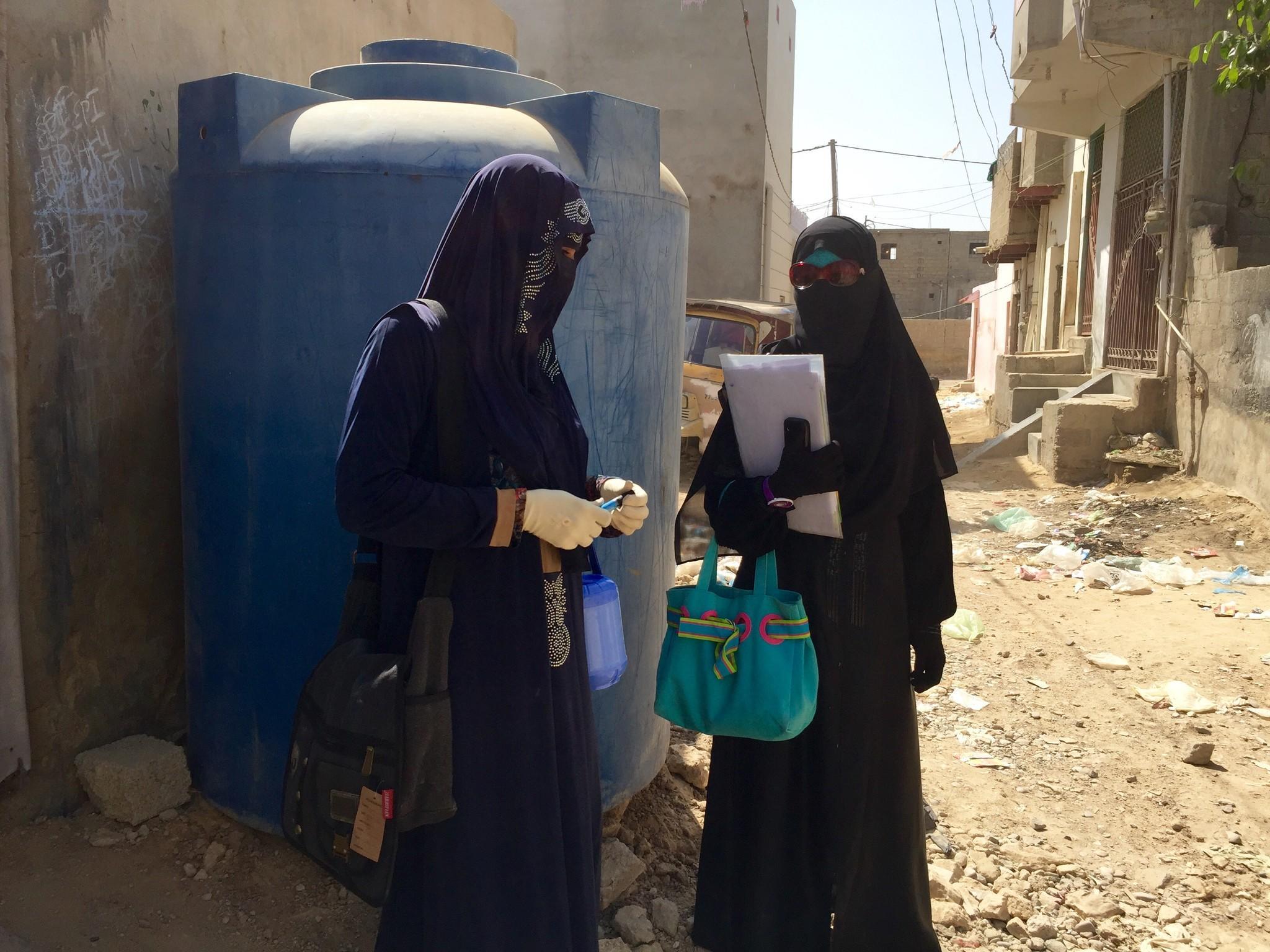 Saira Nizamuddin, right, confers with a fellow polio vaccinator.