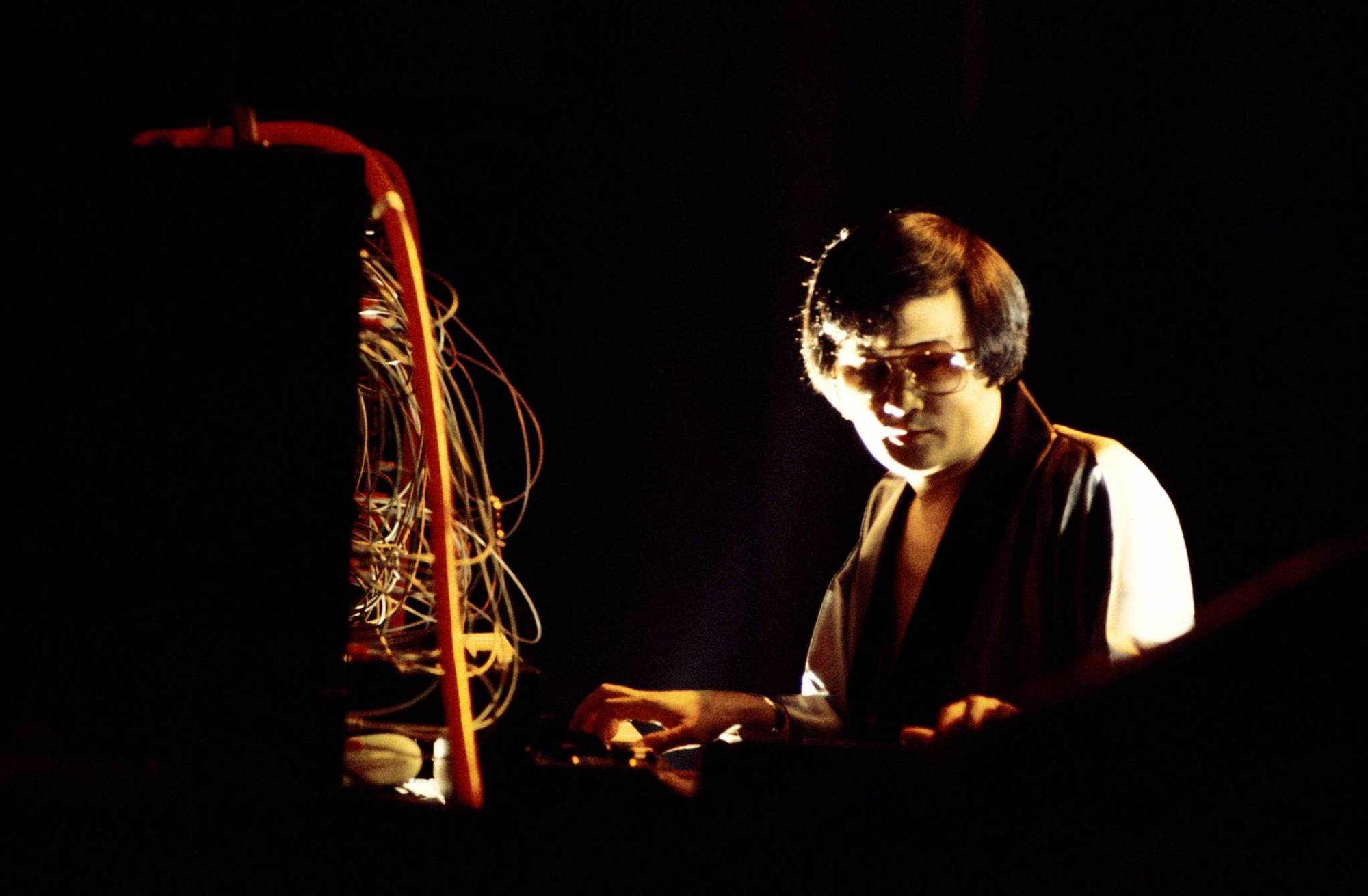 Isao Tomita performing on a synthesizer, as patch cords dangle above the keyboard.
