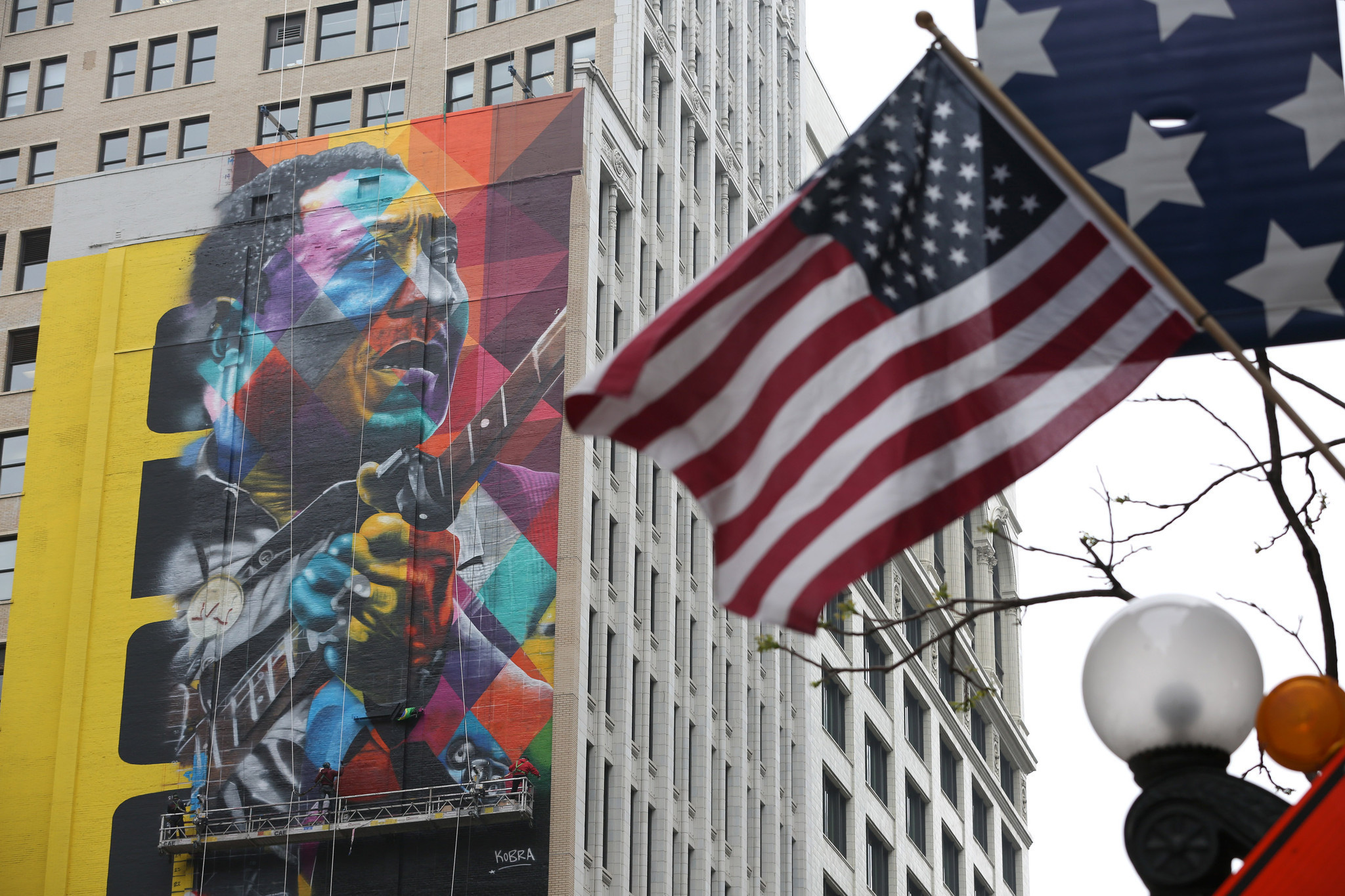 Brazilian street artist painting muddy waters mural in for Chicago mural artist