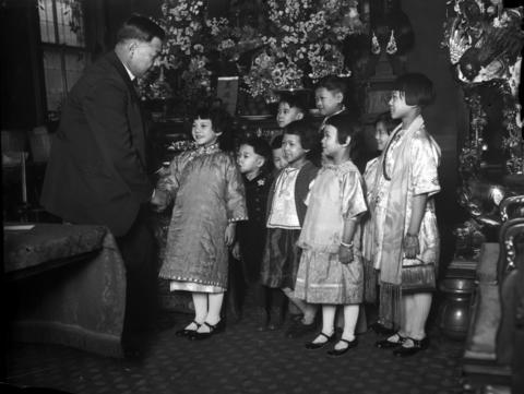Frank Moy, left, considered the mayor of Chinatown, celebrates the Chinese New Year with children in Chinatown in 1934.