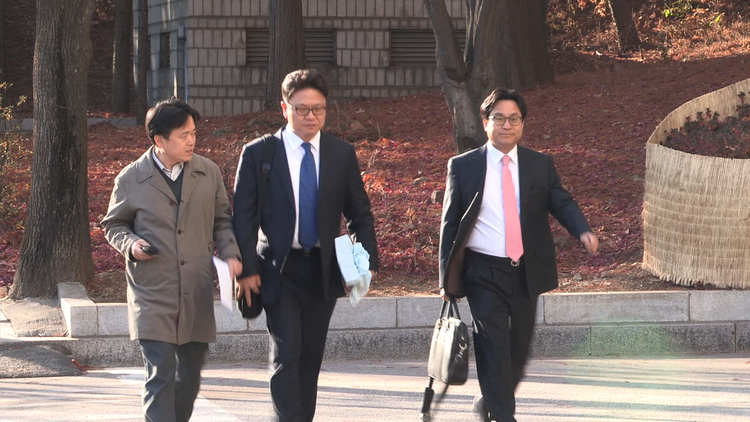 Director Choi Seung-ho questions National Intelligence Service officials as they arrive at their office in Seoul.